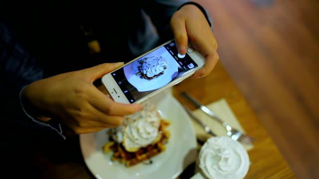 vídeos y material grabado en eventos de stock de woman photographing food with smart phone - modales de mesa