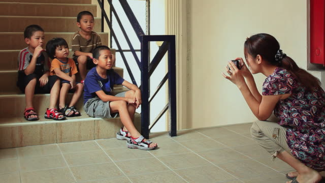ws woman photographing four sons (8-9, 6-7,4-5, 2-3) sitting on stairs / watthana, bangkok, thailand - しゃがむ点の映像素材/bロール