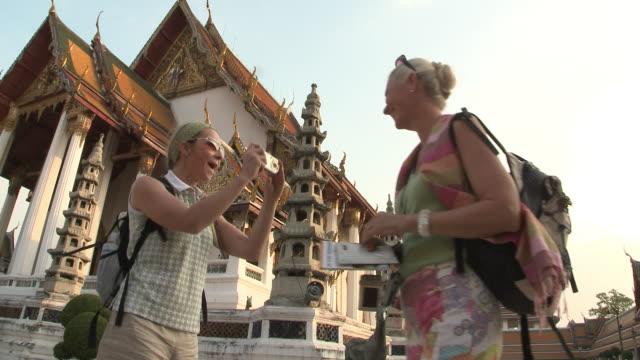 MS LA Woman photographing friend at Wat Phra Kaew (Temple of the Emerald Buddha), Bangkok, Thailand