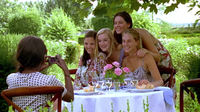 ms, woman photographing friends at garden table, saint ferme, gironde, france - ナイトイン点の映像素材/bロール