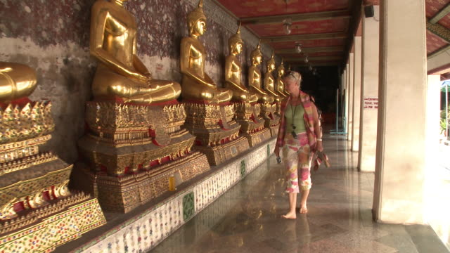 WS DS. MS Woman photographing golden Buddha statue at Wat Phra Kaew (Temple of the Emerald Buddha), Bangkok, Thailand
