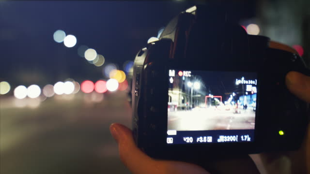 pov woman photographing night scenes in the city. - photographing stock videos & royalty-free footage