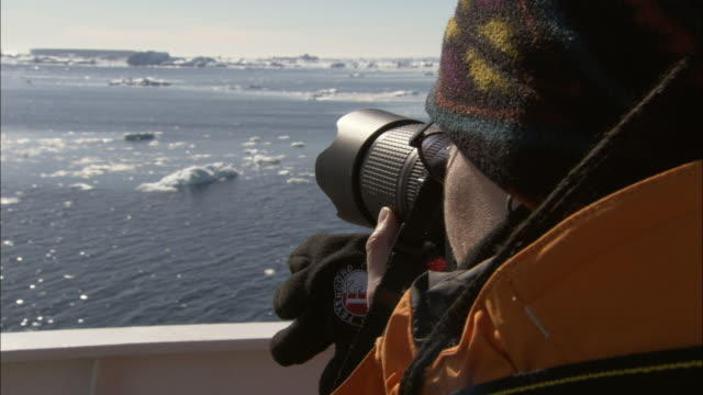 zi, ecu, woman photographing sea with ice floes from ship, antarctica - antarctica research stock videos & royalty-free footage