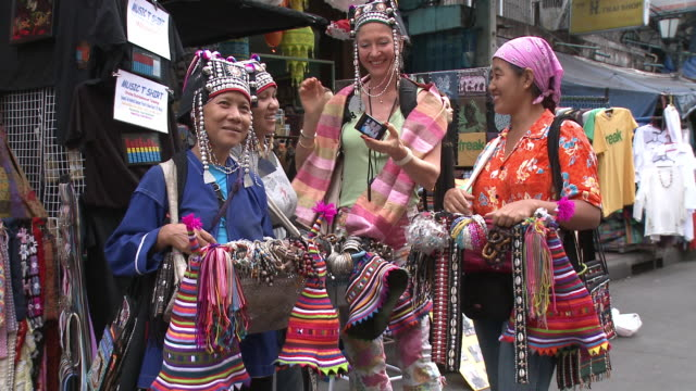 MS Woman photographing self with female market vendors holding traditional hats, Bangkok, Thailand