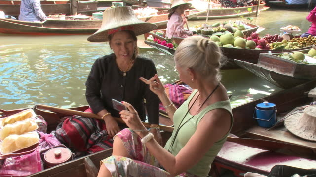 ms woman photographing self with fruit seller on damnoen saduak floating market, bangkok, thailand - tourist stock-videos und b-roll-filmmaterial