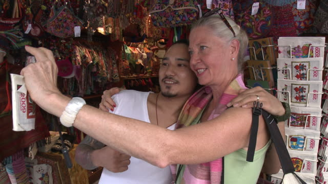 CU ZI ZO Woman photographing self with gift shop owner, Bangkok, Thailand