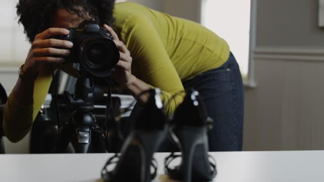 vidéos et rushes de ms tu r/f woman photographing shoes in photographic studio / orem, utah, usa  - orem