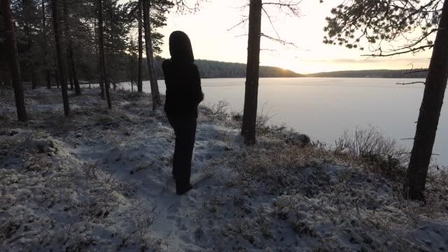 Woman photographing the sunrise at Pallas-Yllästunturi National Park, Lapland, Finland