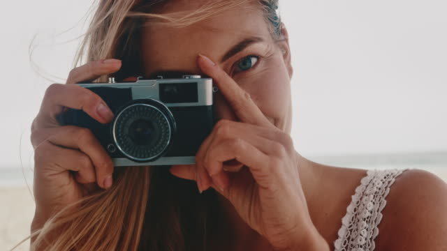 woman photographing through camera at beach - human face photos stock videos & royalty-free footage