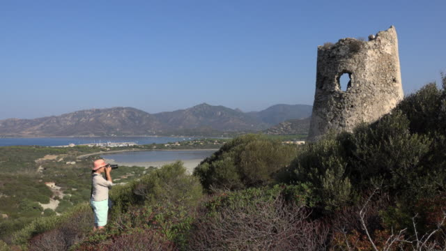 woman photographing torre di porto giunco at villasimius beach - spiaggia stock videos & royalty-free footage