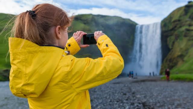 Woman photographing waterfall