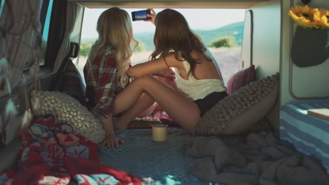 vídeos de stock e filmes b-roll de woman photographing while camping with friend - camping