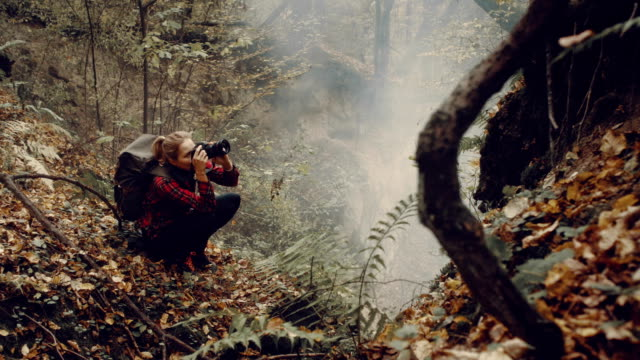 Woman photographing wilderness area. Autumnal landscape