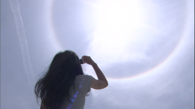 A woman photographs a halo around the sun.