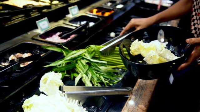 woman pick raw vegetables morning glory into basket plastic for sukiyaki shabu meal - sukiyaki stock videos and b-roll footage