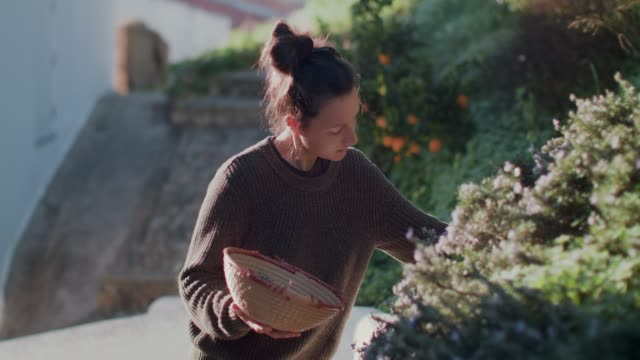 stockvideo's en b-roll-footage met woman picking and smelling fresh herbs on patio - new age