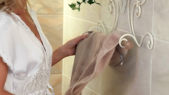 woman picking bath towel from towel rail - towel stock videos & royalty-free footage