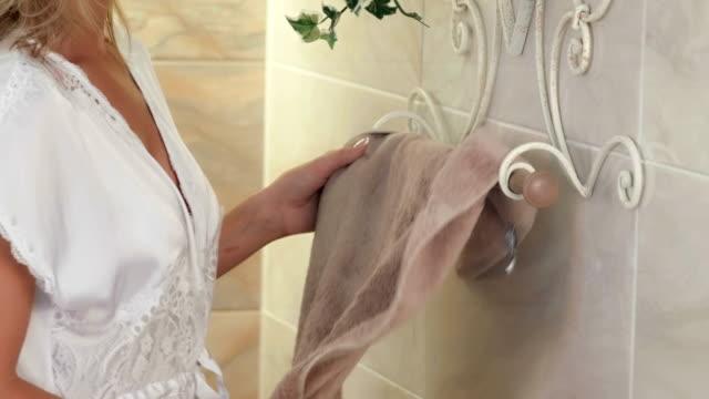 Woman picking bath towel from towel rail