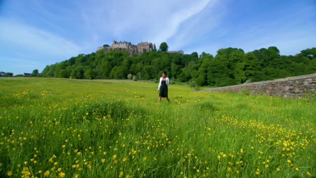 Woman Picking Buttercups In Front Of Stirling Castle, Stirlingshire, Scotland