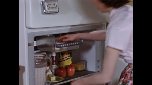 ms woman picking eggs and butter from fridge / united states - refrigerator stock videos and b-roll footage