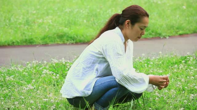 MS Woman picking flowers in park / Shibuya, Tokyo, Japan