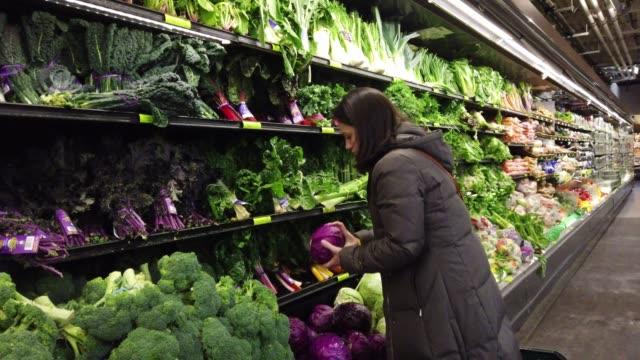 vidéos et rushes de femme cueillant le fruit au marché - acheter