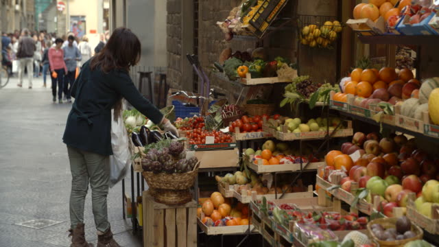 Woman picking fruit from a stall / Florence, Italy