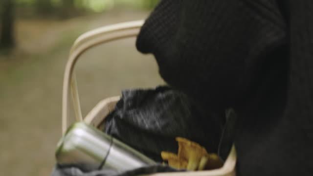 vídeos y material grabado en eventos de stock de mujer recogiendo setas y tomando café en el bosque - cesta de picnic