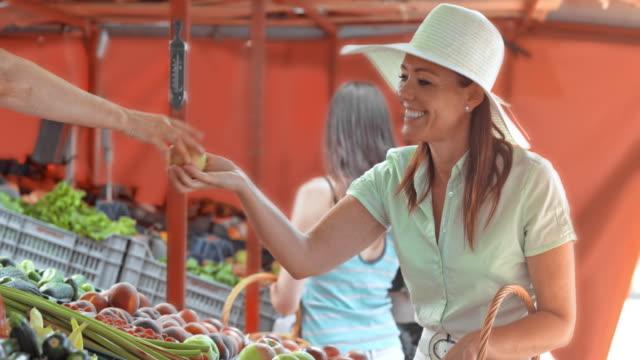 Tome PAN mujer ejercicio manzanas en el puesto de mercado