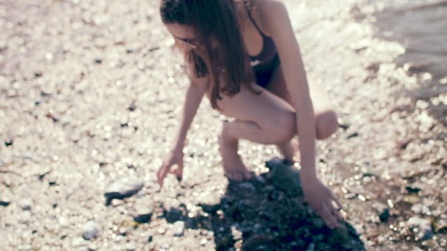woman picking pebbles on beach, skipping rocks - one piece swimsuit stock videos and b-roll footage