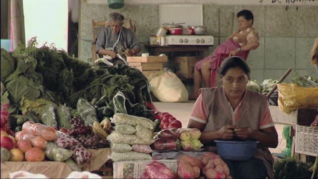 ms tu woman picking through vegetables in farmers market / ecuador  - 男性と複数の女性点の映像素材/bロール
