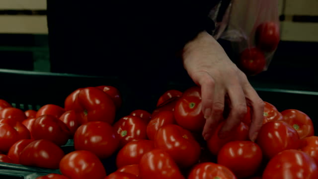Woman picking tomatoes from box in supermarket