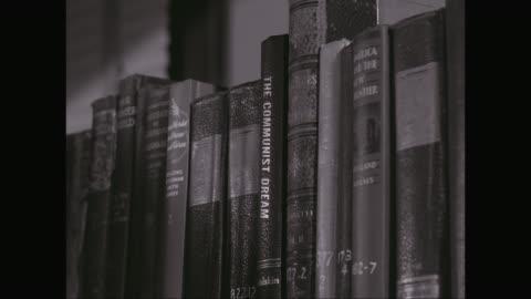vidéos et rushes de cu woman picking up book from shelf / united states - communisme