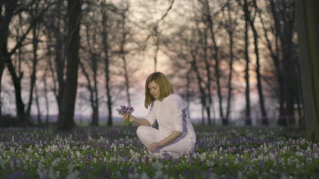 DS vrouw oppakken van bloemen in het park bij zonsondergang