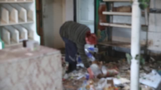 woman picking up garbage and debris in damaged business. workers clean up a small market which was damaged by shelling, and where products litter the... - ukraine stock videos & royalty-free footage