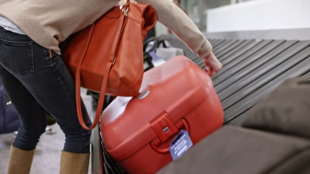 woman picking up her travel bag from the baggage carousel at the airport - bagaglio video stock e b–roll