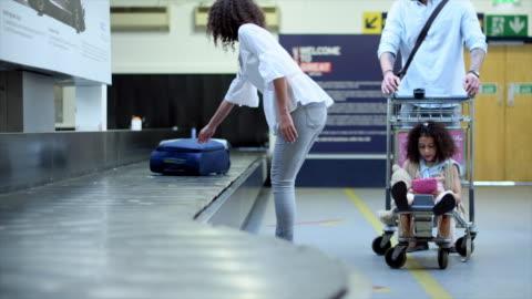vídeos de stock, filmes e b-roll de woman picking up luggage - mala de rodinhas