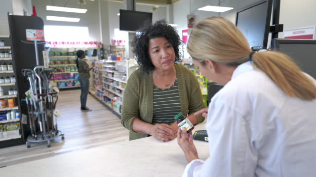 woman picking up prescription at pharmacy - pharmacy stock videos & royalty-free footage