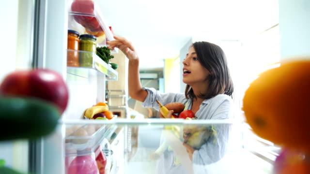 vídeos y material grabado en eventos de stock de mujer recogiendo algunas frutas y verduras de la nevera timelapse. - frigorífico