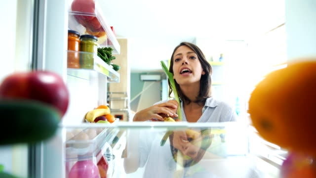 woman picking up some fruits and veggies from the fridge. - cucina domestica video stock e b–roll
