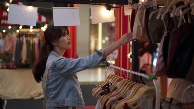 vídeos de stock, filmes e b-roll de woman picks clothes from rack, close up - jaqueta jeans