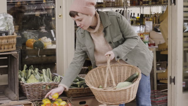 woman picks organic tomatoes and put them in shopping basket at organic food shop. - shopping basket stock videos and b-roll footage