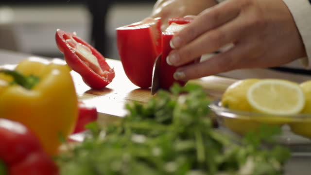 woman picks up and slices a red pepper - peperone video stock e b–roll