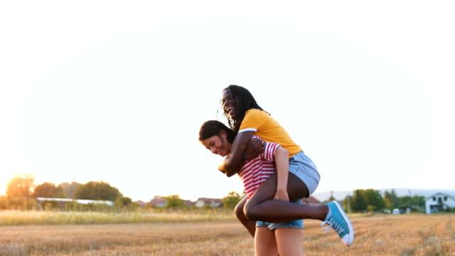 woman piggyback her bestfriend - portare a cavalluccio video stock e b–roll
