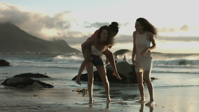 woman piggybacking friend at beach - stare in piedi video stock e b–roll