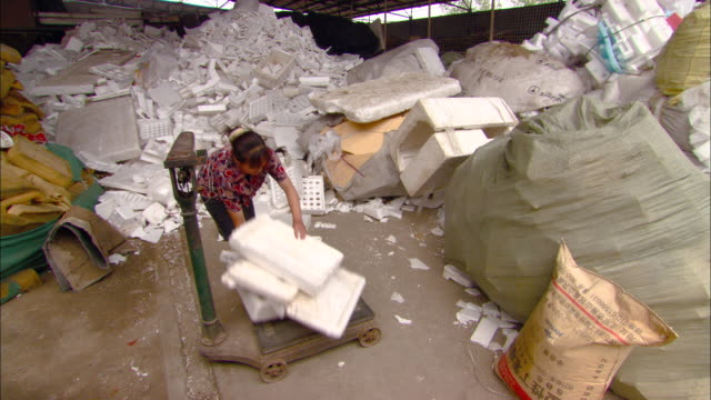 ws woman piling discarded styrofoam onto old scale at recycling center, beijing, beijing, china - polystyrene stock videos & royalty-free footage