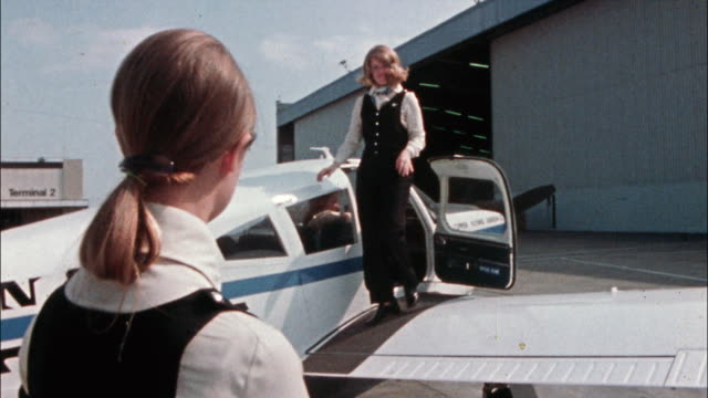 a woman pilot and two passengers exit a single-engine airplane and walk toward a hangar. - captain stock videos & royalty-free footage