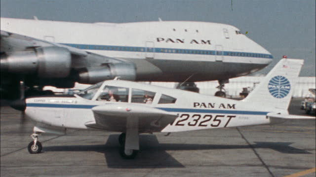A woman pilot taxis a single-engine airplane past a Boeing Pan Am 747 parked on a tramac.