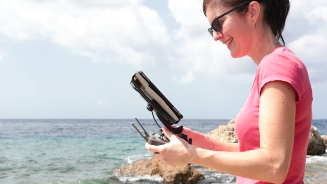 woman pilot using drone remote controller with a tablet mount - drone pilot stock videos and b-roll footage