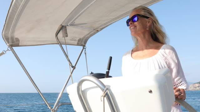 stockvideo's en b-roll-footage met woman pilots sailing yacht on open sea - alleen oudere vrouwen